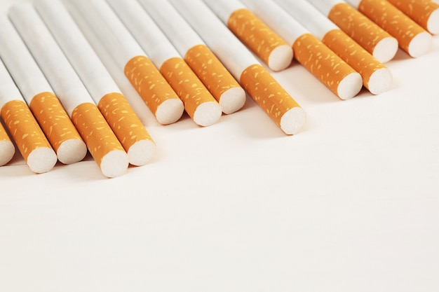 Image of several commercially made pile cigarette on white  background. or non smoking campaign concept, tobacco pattern top view.