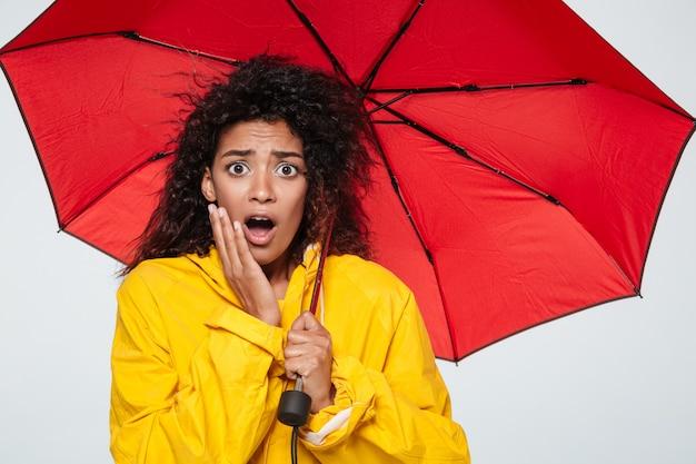 Image of shocked african woman in raincoat hiding under umbrella