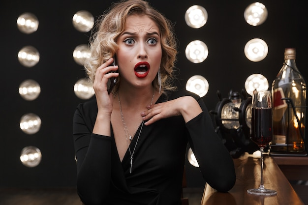 Image of shocked blonde woman wearing elegant dress talking on cellphone and drinking red wine in bar