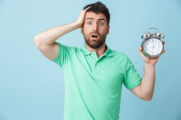 Image of shocked confused young handsome bearded man posing isolated over blue wall holding alarm clock.