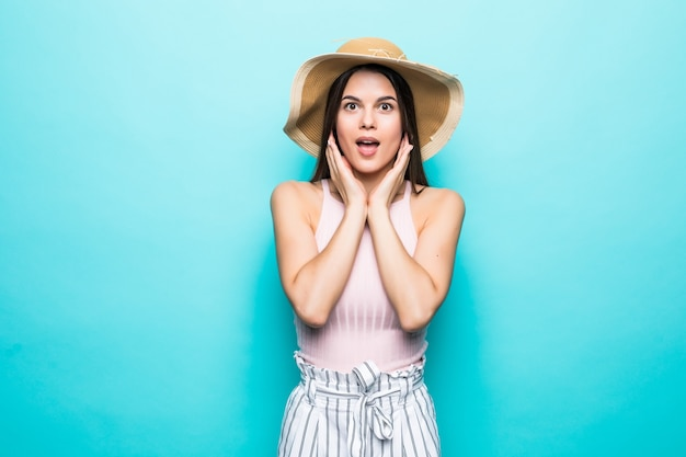 Image of shocked excited young lady standing isolated over blue wall.. looking camera.