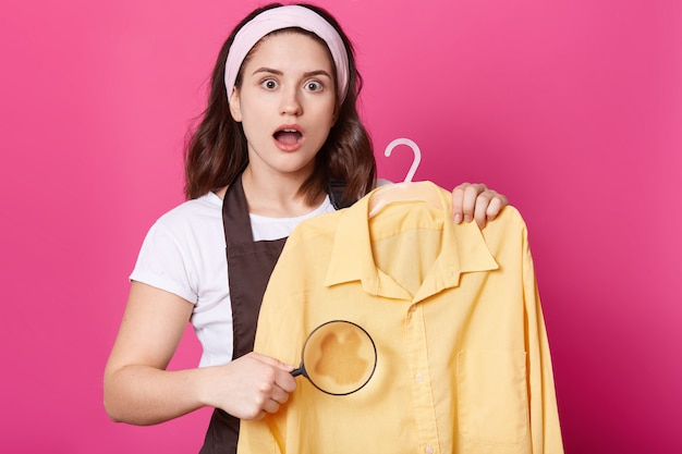 Image of shocked female wears white t shirt, brown apron and hair band, holds yellow shirt and magnifier in hand, looks at camera with astonishment, posing with opened mouth against pink wall