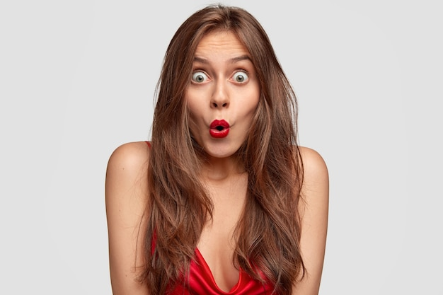 L'immagine della giovane femmina dagli occhi verdi scioccata tiene la bocca rotonda, ha un rossetto rosso