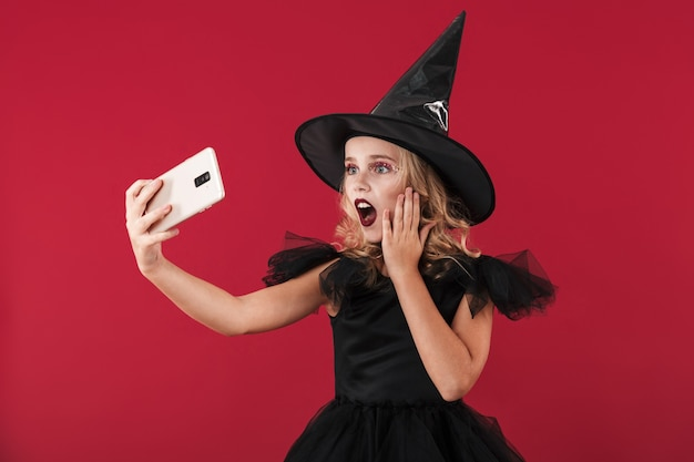 Image of shocked little girl witch in carnival halloween costume