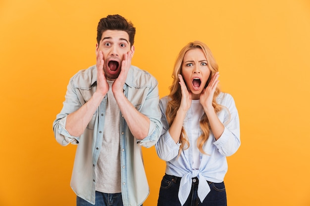 Image of shocked people man and woman in basic clothing expressing surprise or fright with open mouth, isolated over yellow wall