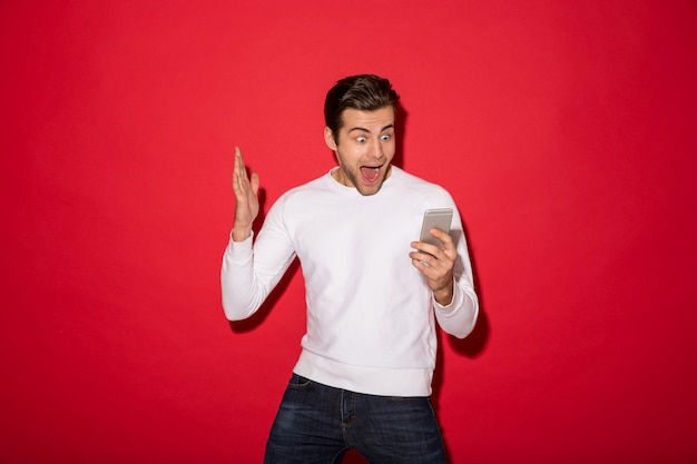 Image of shocked screaming man in sweater looking at smatphone over red wall