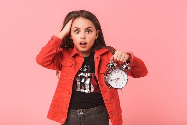 Image of shocked teen girl in casual holding alarm clock while standing, isolated over red wall