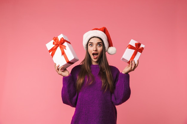 Image of a shocked young emotional woman posing isolated over pink space holding gift boxes wearing christmas hat.