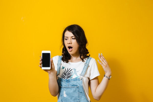 Image of a shocked young girl looking at mobile phone isolated over yellow  wall