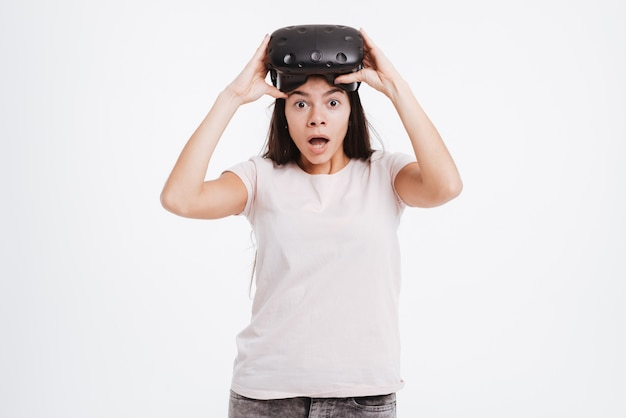 Image of shocked young lady wearing virtual reality device . look at front.
