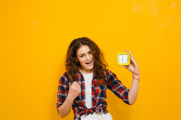 Image shocked young woman  isolated over yellow wall, showing alarm clock