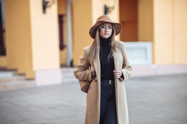 Image-shot молодой привлекательной женщины в пальто и фетровой шляпе на размытом фоне города