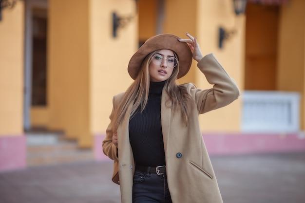 街のぼやけた背景にコートとフェルトの帽子をかぶっている若い魅力的な女性の画像ショット