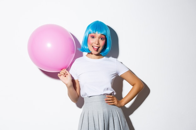 Image of silly party girl in blue wig celebrating holiday, holding pink balloon and showing tongue, standing backgound.
