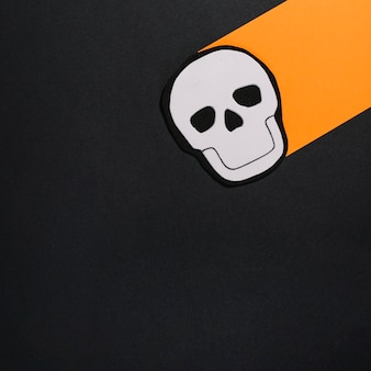 Image of skull on sheet of orange paper