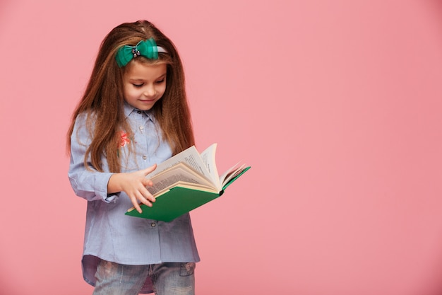 Image of smart schoolgirl with long auburn hair reading interesting book