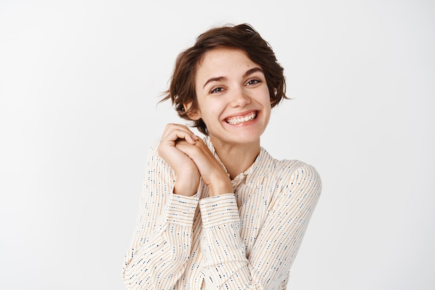 Image of smiling beautiful woman admire something beautiful, looking at lovely, standing against white wall