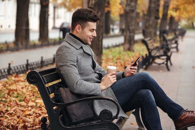 Image of smiling brunette male in coat and jeans drinking takeaway coffee and using his mobile phone, while sitting on bench in park