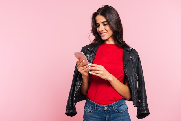 Image of smiling brunette woman using smartphone over pink
