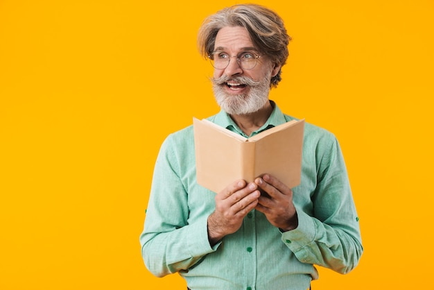 Image of smiling grey-haired bearded man in blue shirt posing isolated on yellow wall reading book.