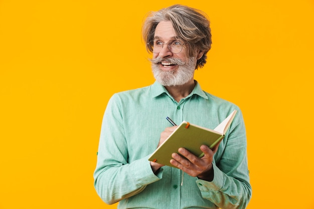 Image of smiling grey-haired bearded man in blue shirt posing isolated on yellow wall writing notes in notebook.