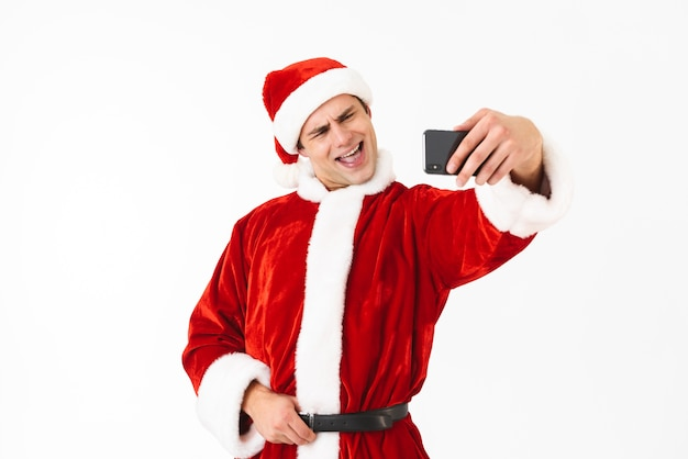 Image of smiling man 30s in santa claus costume holding smartphone and taking selfie