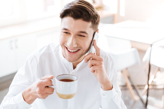 Image of smiling man dressed in white shirt drinking coffee and talking by phone. coworking. looking aside.