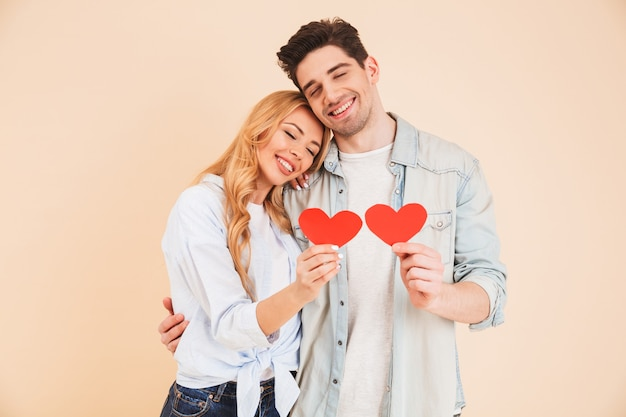 Image of smiling man and woman in love wearing denim clothing hugging together with closed eyes and holding two red paper hearts, isolated over beige wall