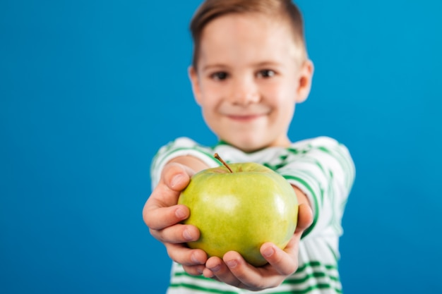 Image of smiling young boy giving apple