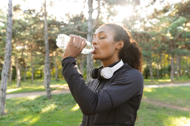 Image of sportswoman 20s wearing black tracksuit and headphones, drinking water while walking through green park