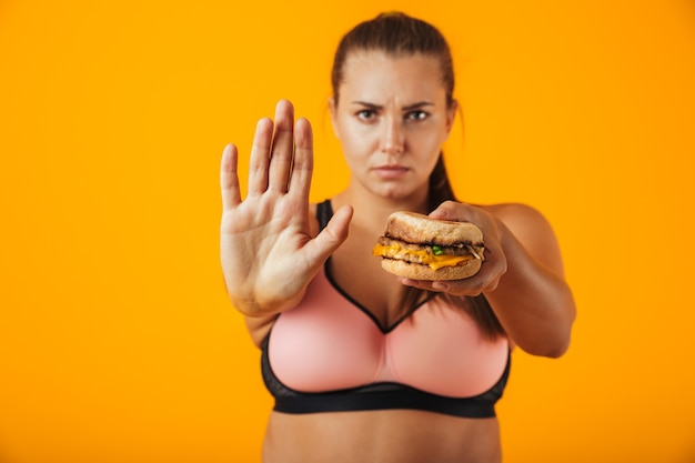 Image of strict chubby woman in tracksuit doing stop gesture while holding sandwich, isolated over yellow background