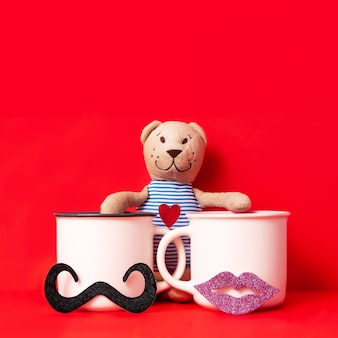 Image of stuffed toy teddy bear and couple cups of coffee with female lips and male mustache, dating on valentine's day celebration concept.