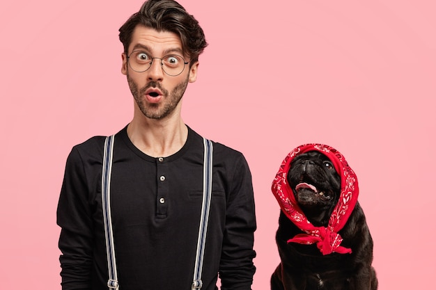 Image of stupefied young male photographer in fashionable clothes, poses together with his lovely pet, isolated over pink wall. black pedigree dog wears stylish red bandana on head.