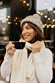 Immagine di styling donna europea in berretto lavorato a maglia e sciarpa bere caffè e godersi il tempo fuori in inverno