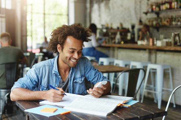 Image of stylish african student with earring wearing denim shirt sitting at wooden table doing his homework holding smartphone being happy to recieve message from his friend typing something