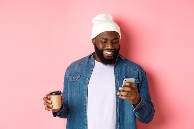 Image of stylish black man hipster drinking takeaway coffee, reading message on phone and smiling, standing over pink background