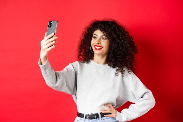 Immagine di una blogger femminile alla moda che si fa selfie sullo smartphone, posa per una foto sul cellulare, in piedi su uno sfondo rosso