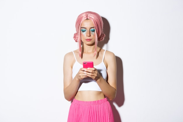 Image of stylish glamour girl in pink wig, looking serious at mobile phone, standing in party outfit.