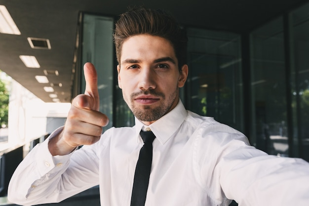 Image of successful businessman dressed in formal suit standing outside glass building, and taking selfie photo