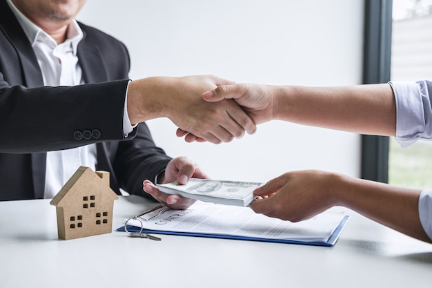 Image of successful deal of real estate, broker and client shaking hands after signing contract approved application form, concerning mortgage loan offer for and house insurance.