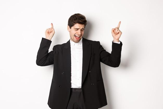 Immagine di un bell'uomo d'affari di successo che balla, si gode la festa, punta le dita in alto e si diverte, in piedi su uno sfondo bianco, indossando un abito nero.