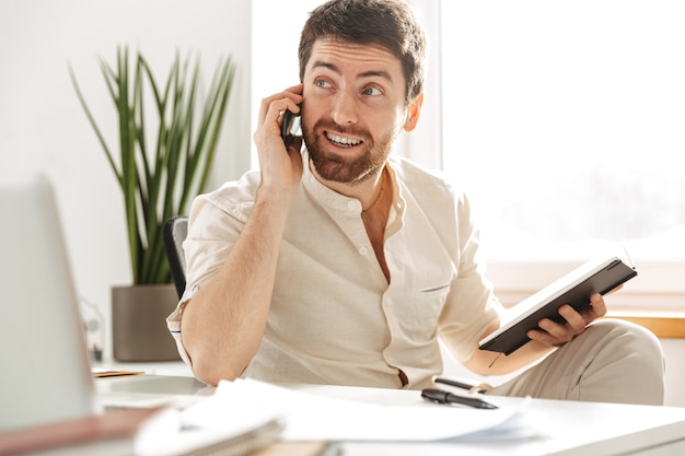 Image of successful office worker 30s wearing white shirt using smartphone and notebook, while sitting at table in modern workplace