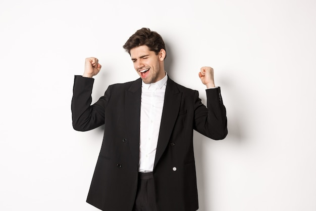 Image of successful and pleased handsome man in suit, rejoicing and making fist pump signs, dancing from happiness, standing over white background.