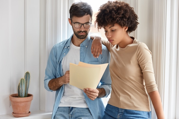 Image of successful young coworkers focused in documents recieved from bank, ready to buy renting apartment, ready to have deal with realtor, stand closely nearwindow, study contract before singing