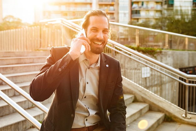 Image of sunlit businesslike man 30s in formal suit laughing to you, while speaking on smartphone and standing on stairs in city centre