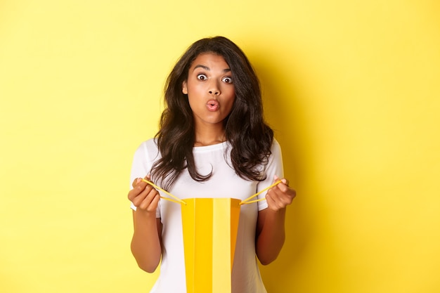 Image of surprised african-american girl receive a gift on holiday, open a shopping bag and looking amazed, standing over yellow background.