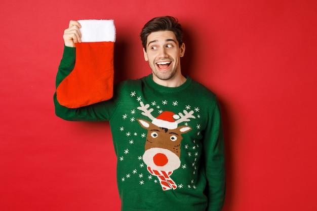 Immagine di un uomo sorpreso e divertito con un maglione verde, che guarda la calza di natale con regali e sorride, in piedi su uno sfondo rosso