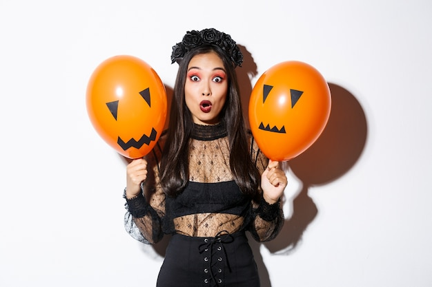 Image of surprised asian woman in witch costume celebrating halloween, holding balloons with scary faces