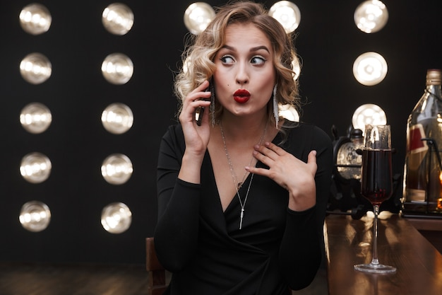 Image of surprised blonde woman wearing elegant dress talking on cellphone and drinking red wine in bar