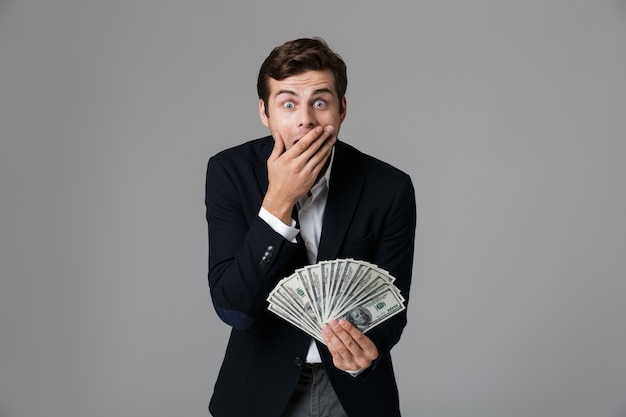 Image of surprised businessman 30s in suit smiling and holding fan of money in dollar banknotes, isolated over gray wall